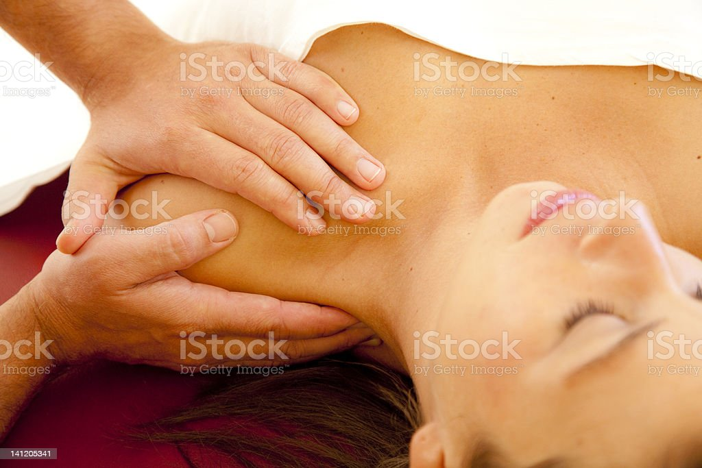 good looking woman receives a massage at her shoulder stock photo