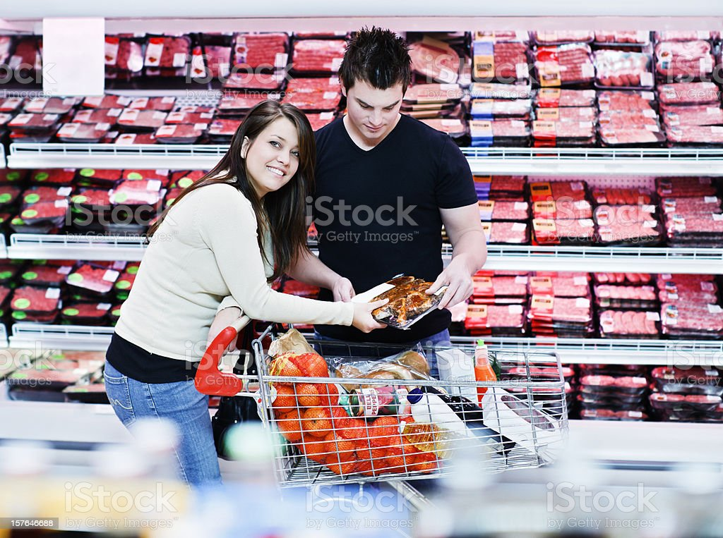 Good looking young couple shop for meat in supermarket royalty-free stock photo
