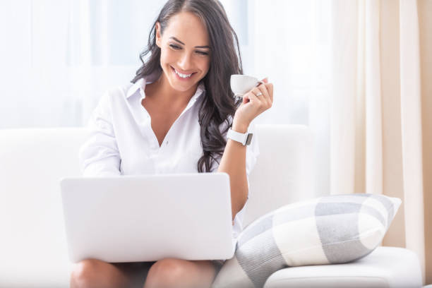 Good looking young female laughing into a laptop on her knees while having a video call during a quarantine, having a coffee in her hand in her house. stock photo