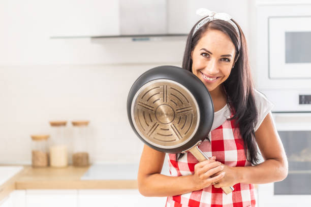 Good looking young housewife smiling at camera standing in the kitchen with a frying pan in her hands. stock photo