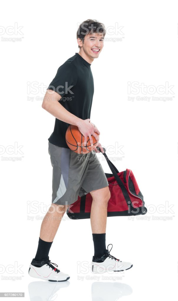 good looking young man holding basketball and sports bag and walking