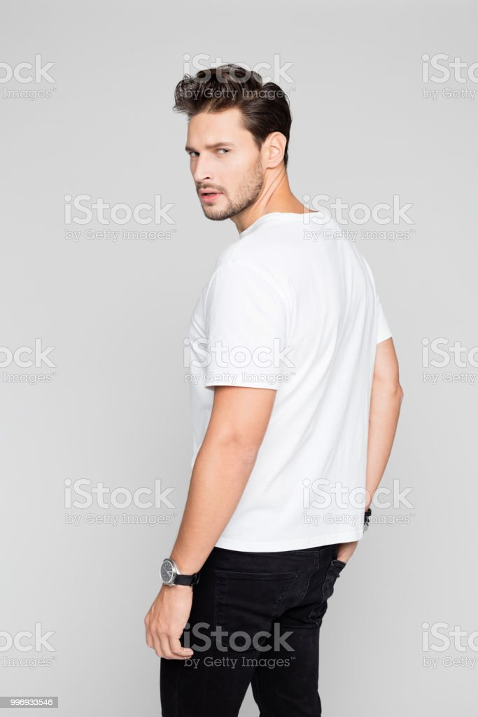 Good looking young man posing in casuals Portrait of good looking young man posing in casuals on grey background 25-29 Years Stock Photo