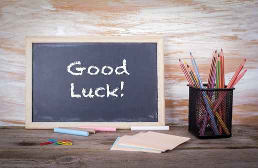 Good luck text on a blackboard. Old wooden table with texture