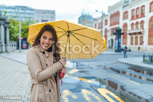 Beautiful woman with umbrella on a rainy day. Good mood at any weather. Attractive young smiling woman carrying umbrella and adjusting her coat while walking by the street