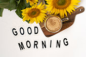 Good Morning. A bouquet of large sunflowers and hot coffee. Sunflower arrangement flat lay style on background white.