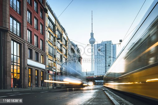 long exposure of yellow street car in Berlin Mitte at sunrise hour in front of TV-Tower