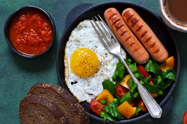 guten morgen! frühstück mit wurst, ei, salat und tomaten sauce mit einer tasse kaffee auf einem konkreten hintergrund. - englischer erbsen salat stock-fotos und bilder