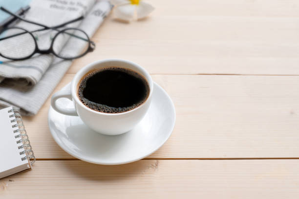 Good morning coffee. Coffee cup on table, blurred newspaper and reading glasses. Good morning coffee. early 20th century stock pictures, royalty-free photos & images