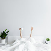 istock good morning concept - female hands with coffee cup and victory sign sticking out from the blanket at home or hotel, copy space over white wall 1279112949