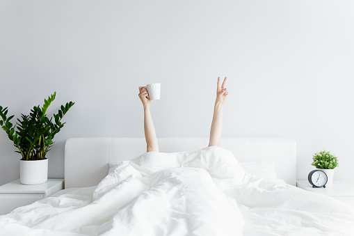 good morning and relaxation concept - female hands with coffee cup and victory sign sticking out from the blanket at home or hotel