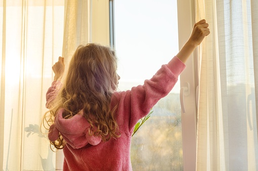istock Good morning. Girl child in pajamas opens curtains and looks out the window. 939135198