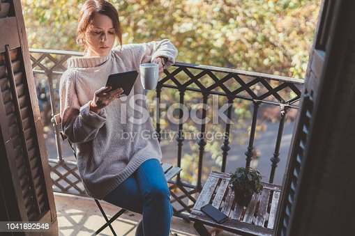 Girl drinking her morning coffee on the terrace in Barcelona