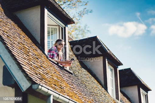 Girl texting on the rooftop window