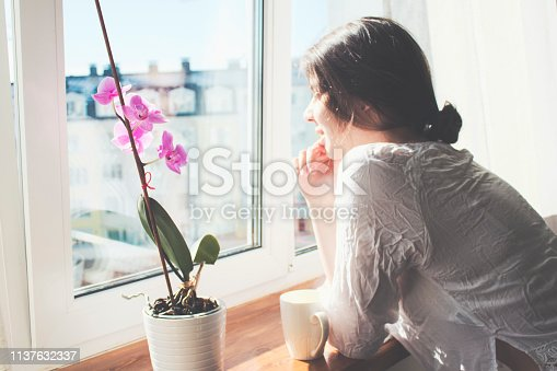 Beautiful girl standing at the window, admiring the view and enjoying the morning coffee