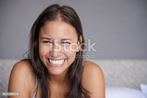 Shot of a beautiful young woman with a big smile sitting on a bedhttp://195.154.178.81/DATA/i_collage/pi/shoots/783637.jpg