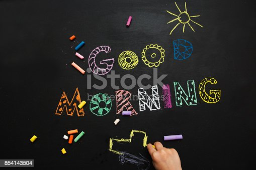 istock good morning. the kid draws on a black slate background. 854143504