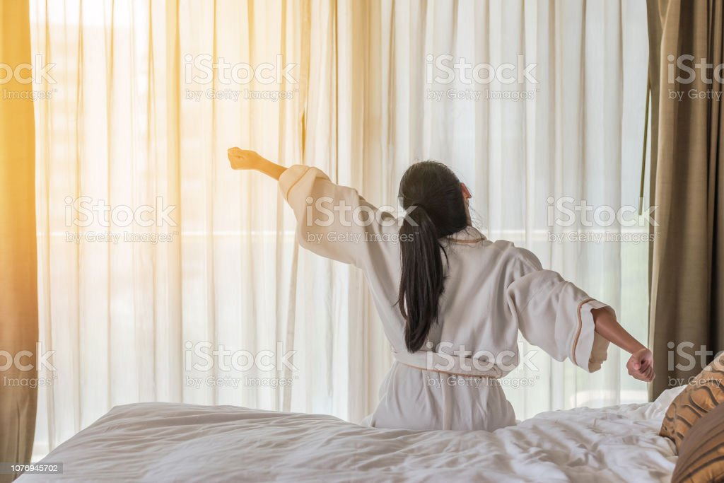 Good morning wake-up with Asian woman relaxing in hotel room