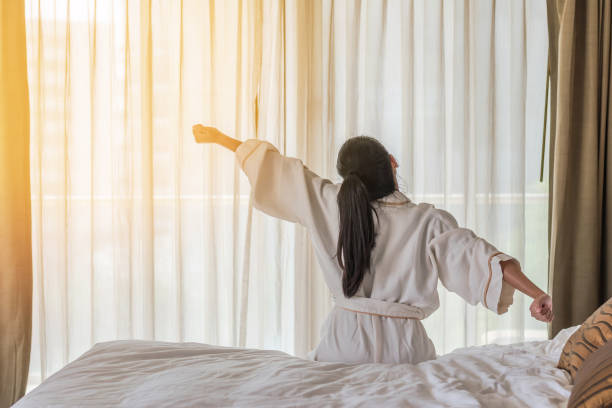 Good morning wake-up with Asian woman relaxing in hotel room Good morning wake-up with Asian woman relaxing in hotel room fresh start morning stock pictures, royalty-free photos & images