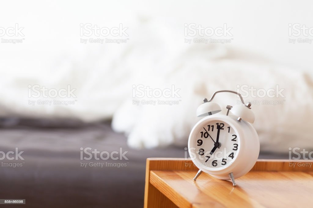 Good morning with alarm clock on bedside table stock photo
