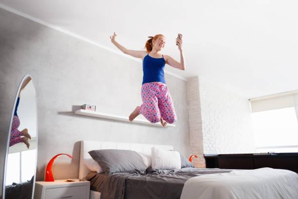 Buenas noticias para la mujer joven feliz niña saltando en la cama - foto de stock