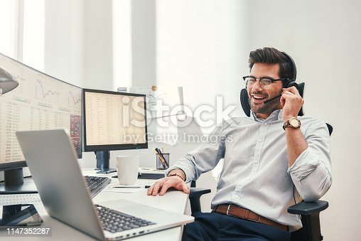 istock Good news. Happy young bearded trader in headset talking with client and smiling while sitting in his modern office. 1147352287