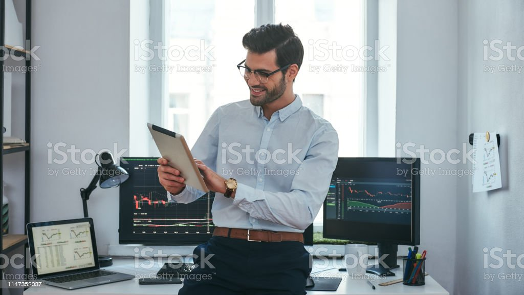 Good news. Happy young trader in formal wear is looking is using his...
