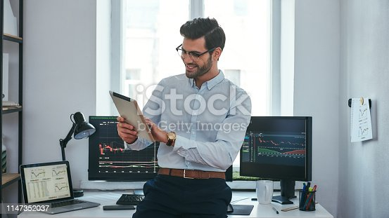 Good news. Happy young trader in formal wear is looking is using his digital tablet and smiling while standing in front of computer screens with trading charts in the office. Forex market. Trade concept. Investment concept