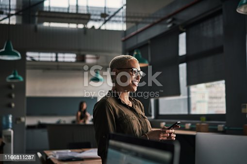 Shot of an attractive young businesswoman using her cellphone at work