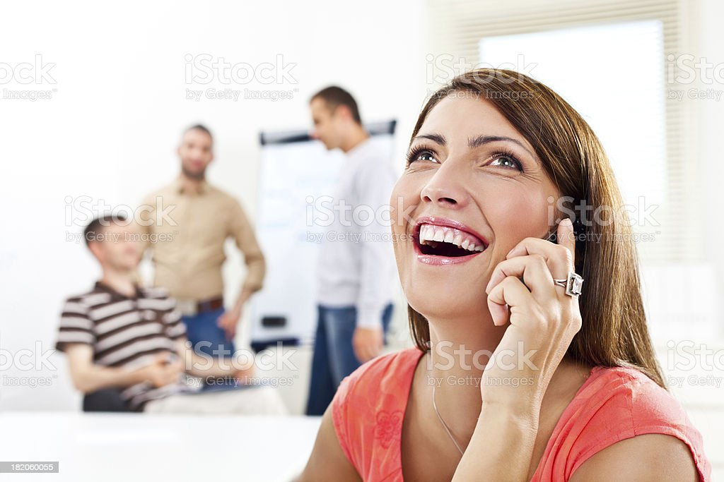 """Good news """"Happy woman talking on phone in an office, while her colleagues discussing in the background."""" 30-34 Years Stock Photo"""