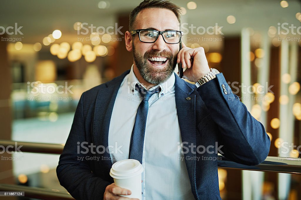Happy businessman with plastic glass speaking on the phone