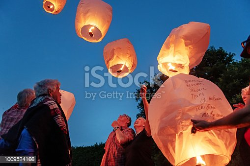 Good old friends having great times together during a summer day, making wishes and let flying chinese lantern at dusk