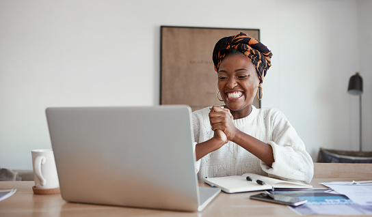Shot of a young woman cheering while working on a laptop at home