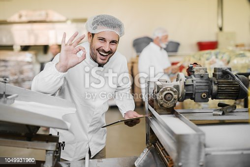 Good quality. Picture of cheerful smiling young man in sterile clothes in food factory. Holding tablet in one hand and with other gesturing that the quality of product is good.