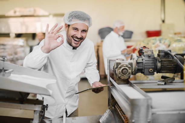 gute qualität. bild von fröhlich lächelnden jungen mann in sterile kleidung im lebensmittelsektor. halten tablet in der hand und mit anderen gestikulieren, die die qualität des produktes ist gut. - nahrungsmittelfabrik stock-fotos und bilder