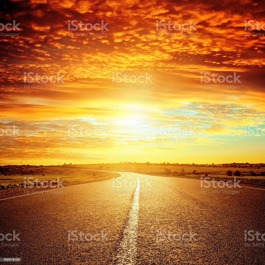 good red sunset and asphalt road to horizon stock photo