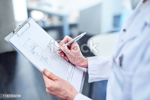 Cropped shot of a medical professional filling out paperwork