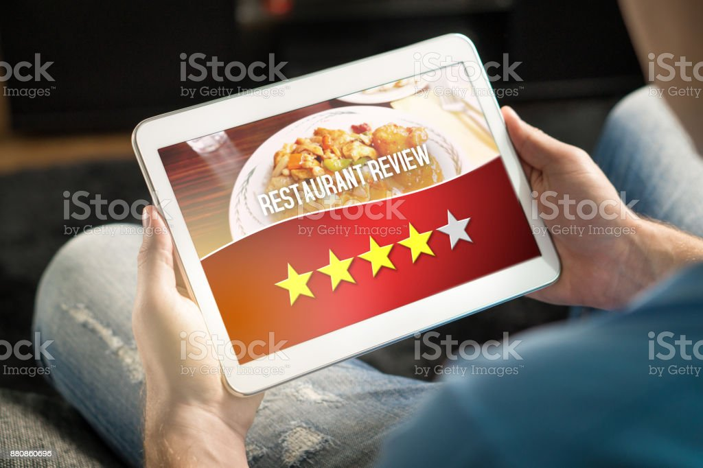 Good review. Satisfied and happy customer giving great rating with tablet on an imaginary criticism site, application or website. stock photo