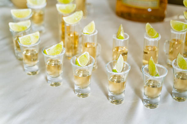 Good service of tequila in small glasses with lime on the white tablecloth. Glasses with vodka, gin, tequila and a slice of lime on them. Good service of tequila in small glasses with lime on the white tablecloth. Glasses with vodka, gin, tequila and a slice of lime on them. tequila shot stock pictures, royalty-free photos & images