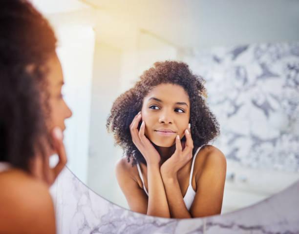 good skincare habits pay off - woman mirror foto e immagini stock