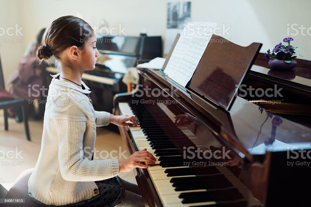 good student plays  piano at a music school stock photo