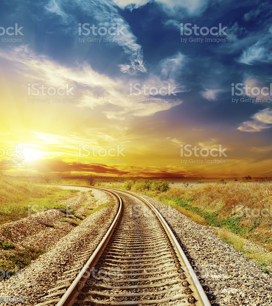 good sunset in colored sky over railroad stock photo