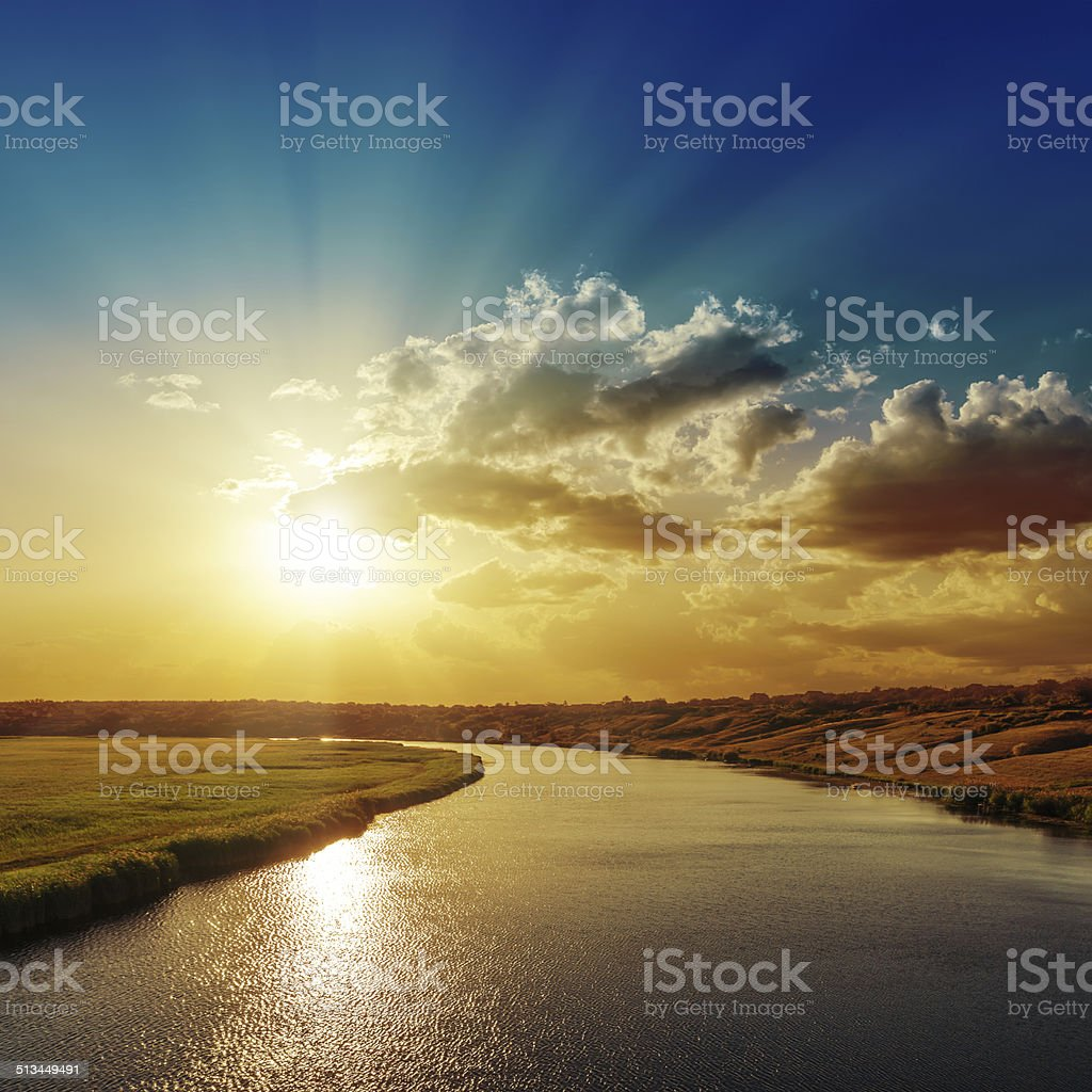 good sunset with rays in clouds over river stock photo
