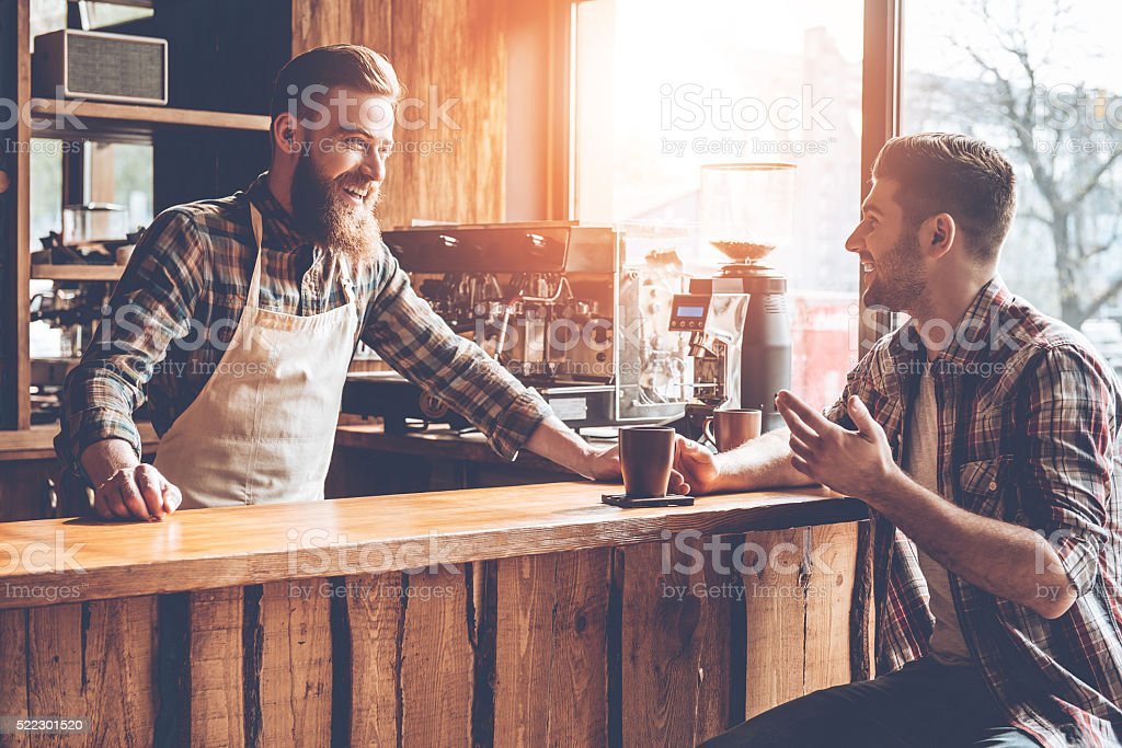 Good talk with customer. Barista and his customer discussing something with smile while sitting at bar counter at cafe Adult Stock Photo
