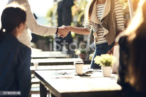 Cropped shot of colleagues shaking hands during a meeting at an outdoor cafe
