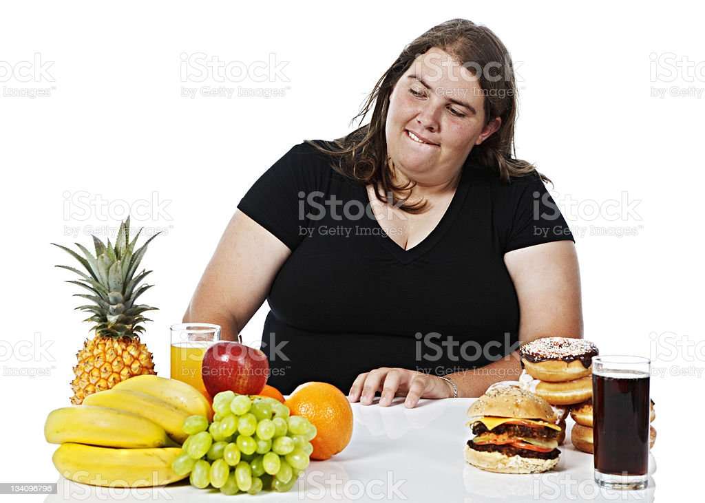 Good versus evil as plump woman deliberates over food choice royalty-free stock photo