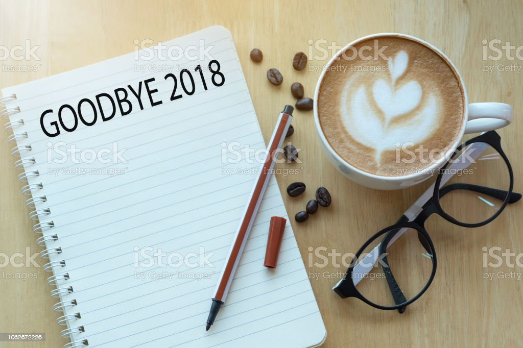 Goodbye 2018 concept on notebook with glasses, pencil and coffee cup on wooden table. stock photo