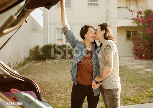 Shot of woman saying goodbye to her girlfriend after loading luggages into car trunk