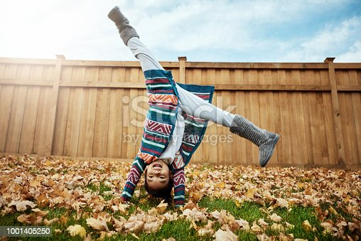 Shot of an adorable little girl doing cartwheels an autumn day outdoors