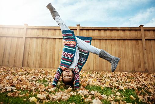 Shot of an adorable little girl doing cartwheels an autumn day outdoors