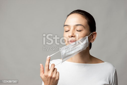 Woman opening her face mask.